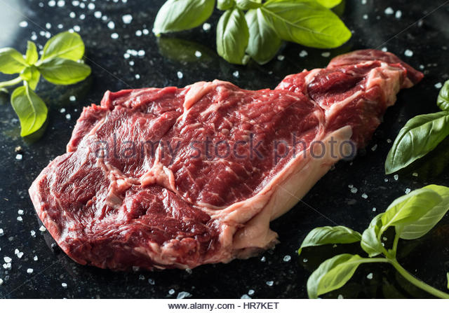 Fresh steak with spices and leafs of basil on marble background. Uncooked meat. Copy space, close up - Stock Image