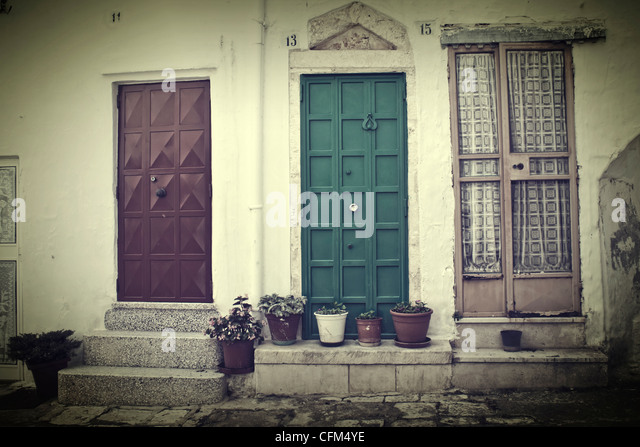 three doors with flower pots in an old Italian houses line - Stock Image