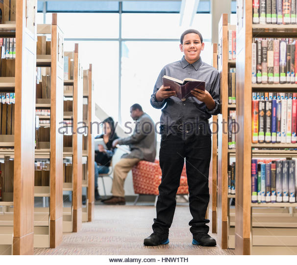 Smiling teenage boy standing in library reading book - Stock-Bilder