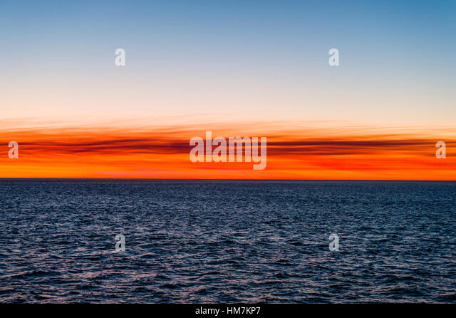 Flaming red afterglow over the ocean horizon at sunset. - Stock-Bilder