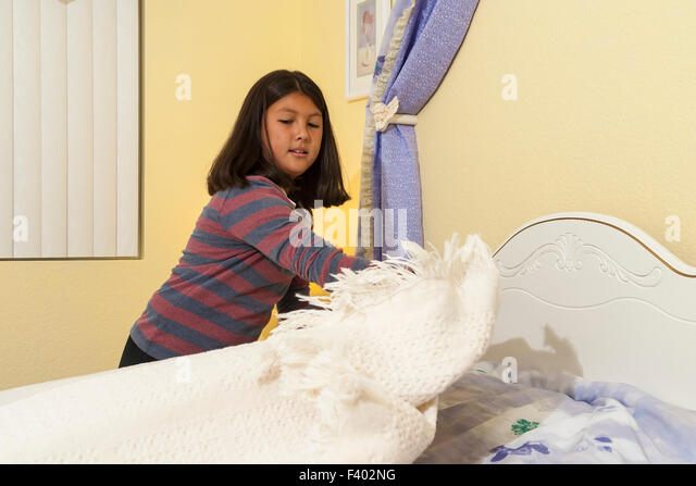 Korean/American teen girl tidying up aged 11-13 year olds making her bed.  Multi racial diverse diversity ethnicity - Stock-Bilder
