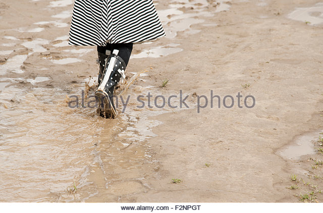 Woman wearing rain boots and walking in puddles - Stock-Bilder