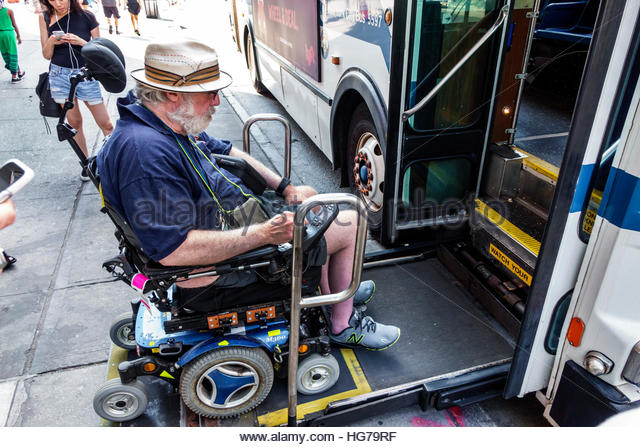 Manhattan New York City NYC NY Chelsea MTA bus stop public transportation man disabled electric wheelchair ADA lift - Stock Image