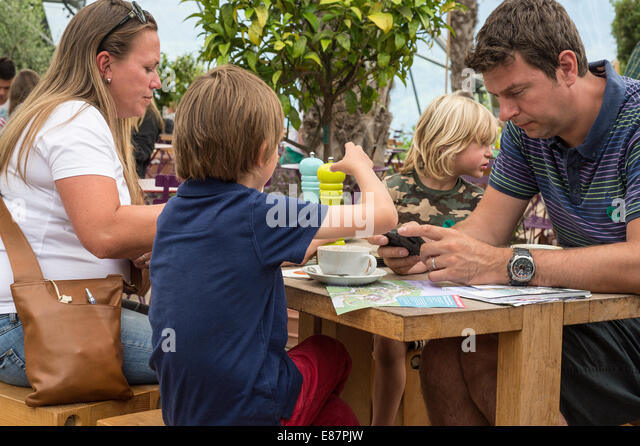 Mobile phone and family on holiday Cornwall England UK August - Stock Image