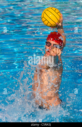 Water Polo player jumps high in pool to shoot for goal. - Stock Image