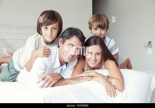 Family lying on bed, portrait - Stock Image