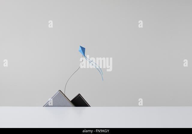 Conceptual Papermade mountain range and kite - Stock Image