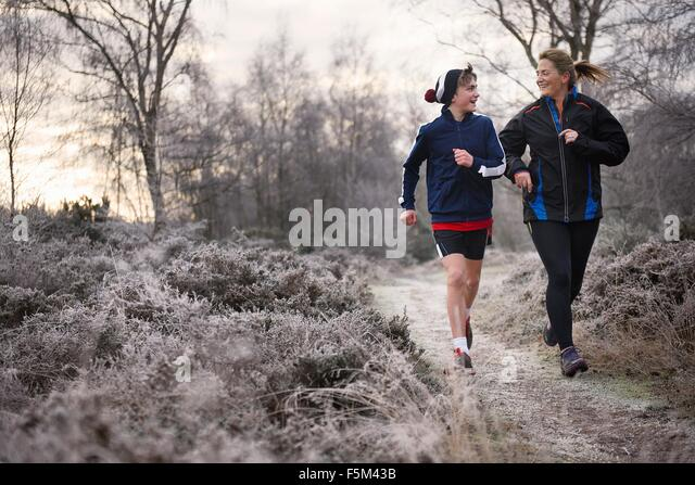 Front view of mother and son running on frosty path face to face smiling - Stock Image