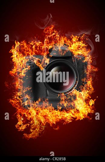 Photo camera with no labels or trademarks on fire - Stock Image