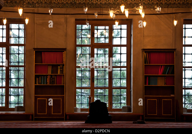 BLUE MOSQUE, Sultan Ahmet Camii - Muslim man praying by the window while outside snowing, Sultanahmet, Istanbul, - Stock Image