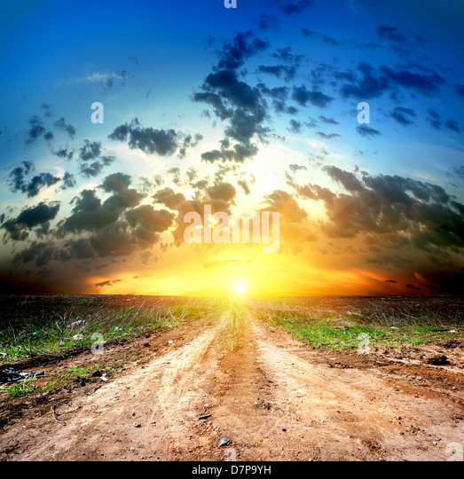 Country road and cumulus clouds in the evening - Stock Image