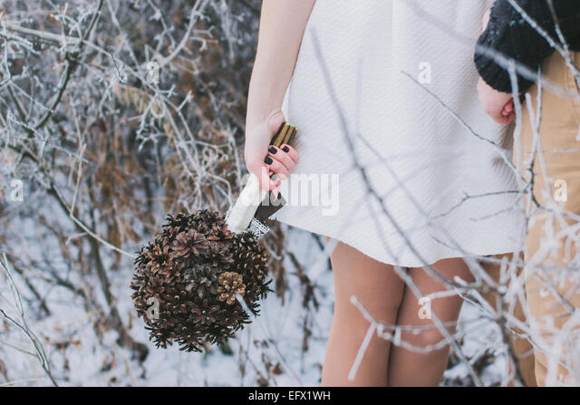 Bride and groom holding hands in snow-covered winter forest; bride holding wedding bouquet made of pine cones - Stock-Bilder