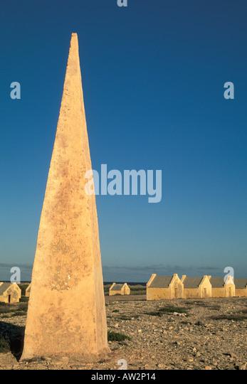Bonaire Netherlands Antilles Obelisk navigation marker with slave huts in background - Stock Image