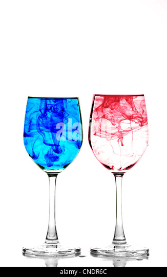 Two wine glasses filled with water and spreading red and blue ink - Stock-Bilder