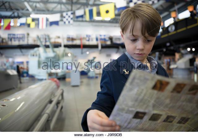 Curious boy looking at brochure in war museum hangar - Stock-Bilder