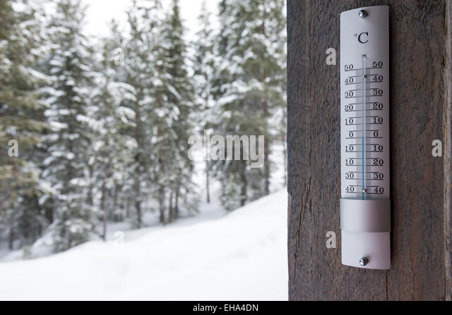 A close up of a thermometer showing zero degrees centigrade with a snowy winter landsacpe in the background - Stock Image