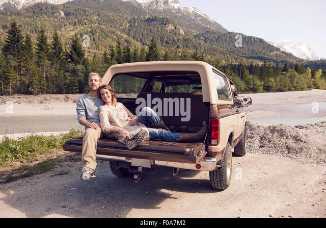 Couple sitting on back of pick up truck, looking at camera, Wallgau, Bavaria, Germany - Stock Image