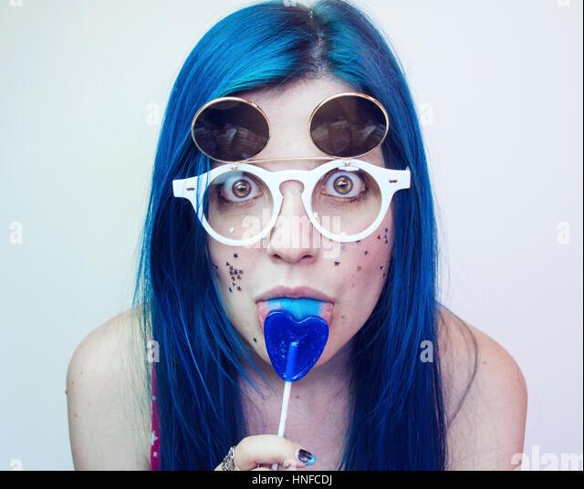 Young woman with blue hair eating a blue heart lollipop - Stock Image