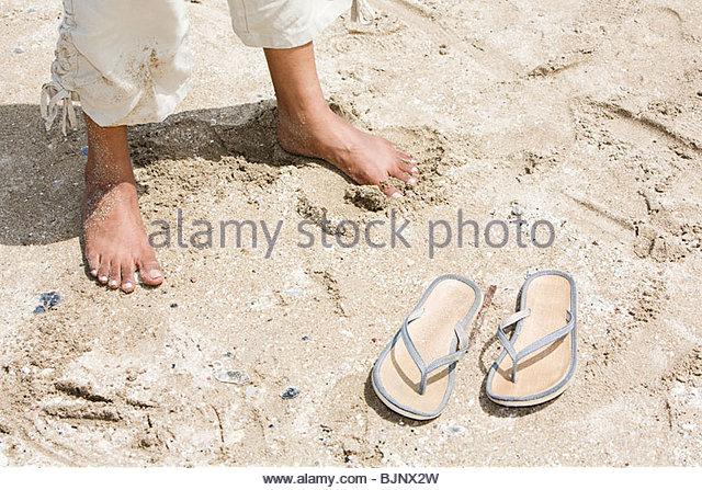 A womans feet on a beach - Stock Image