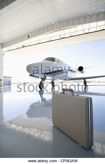 Briefcase in hangar by jet - Stock Image