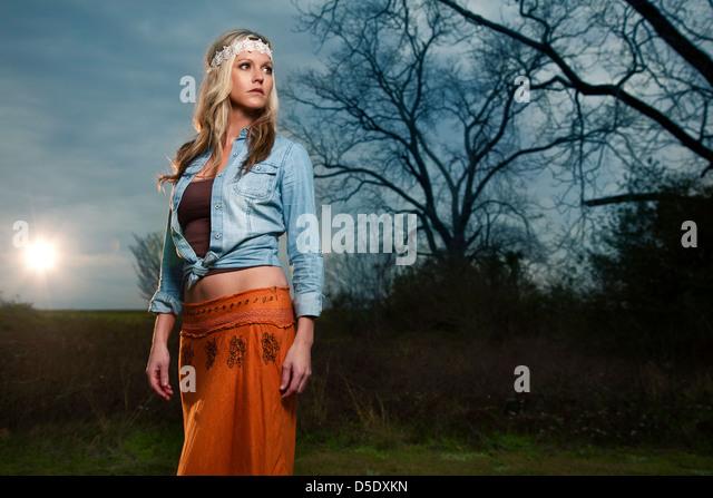Woman in field in vintage dress in field against cloudy sky - Stock-Bilder