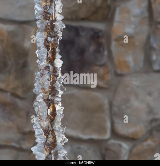 Thick Ice on Rain Chain froze over in winter - Stock Image