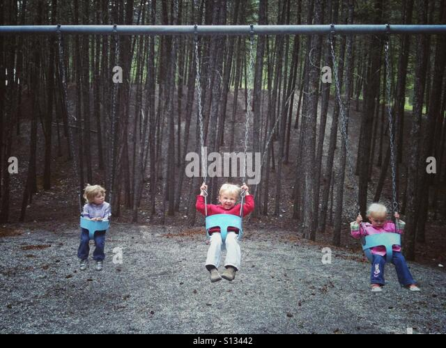Three children on a swing in a mountain forest. - Stock Image