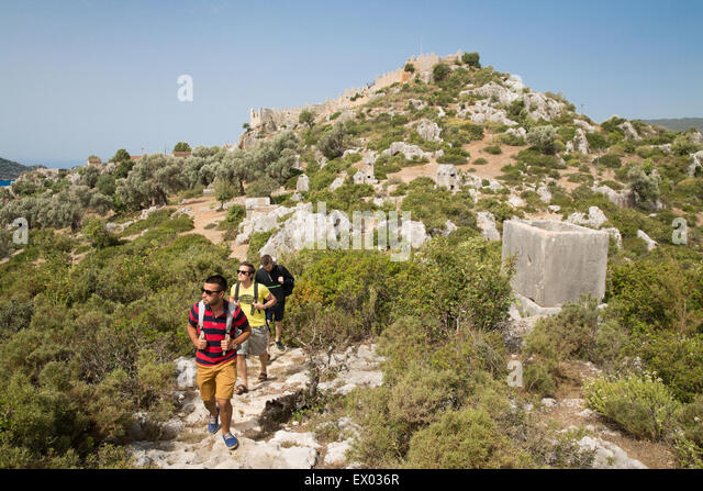 Men trekking near Tombs, Lycian way, Kalekoy, Demre, Simena, Turkey - Stock Image