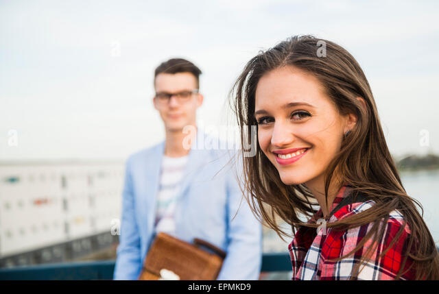Smiling young woman with man in background - Stock Image