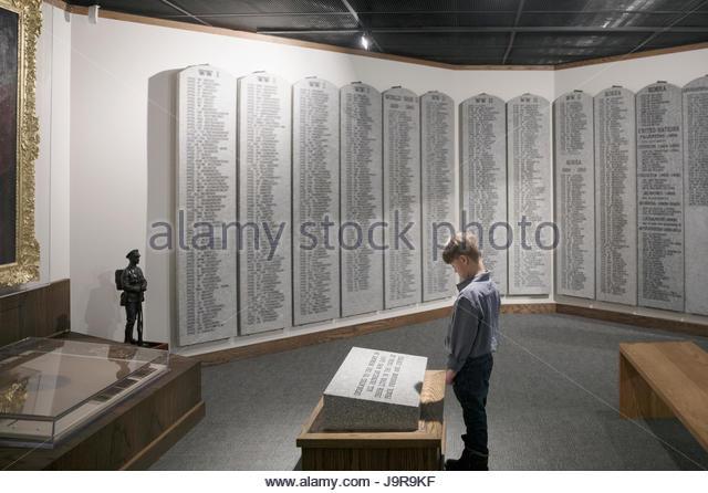Curious boy viewing exhibit plaque in war museum - Stock-Bilder