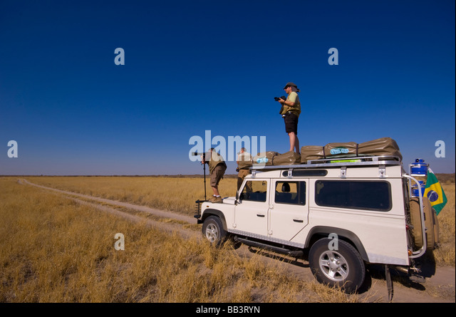 Tourists stopping for pictures by the wide open spaces of the Central Kalahari Park, Botswana - Stock Image