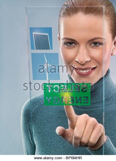 Young woman selecting alternative energy, studio shot - Stock Image