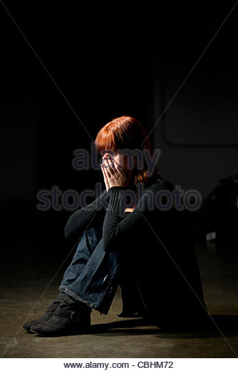 teen girl sitting on a floor in a darkened room looking depressed - Stock Image