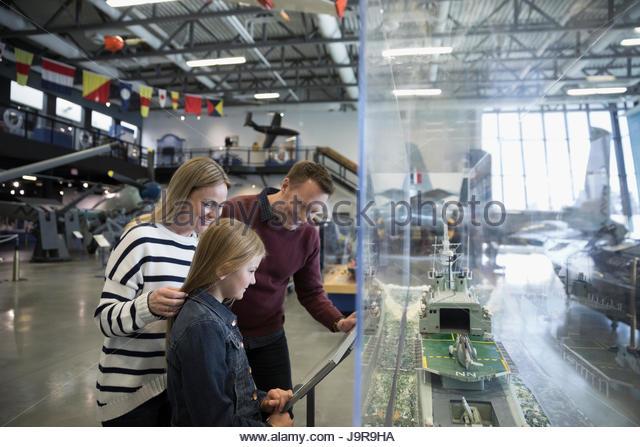 Curious family reading information at Naval ship model exhibit in war museum hangar - Stock-Bilder