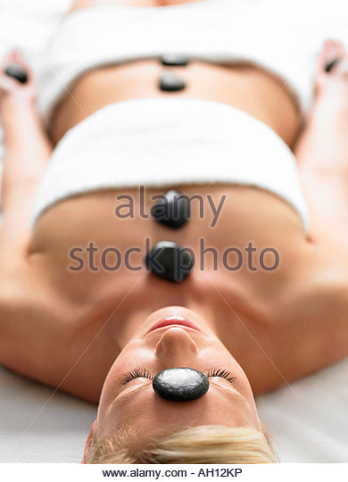 A woman lying in a spa with stones on her body - Stock Image
