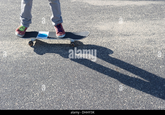 Detail of legs riding skateboard - Stock Image
