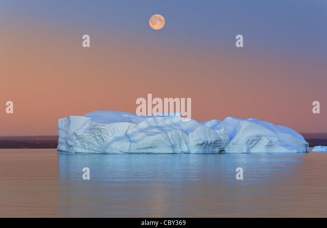 Iceberg at Sunset and Moonrise at Hall Bredning, Scoresby sund, Greenland - Stock Image