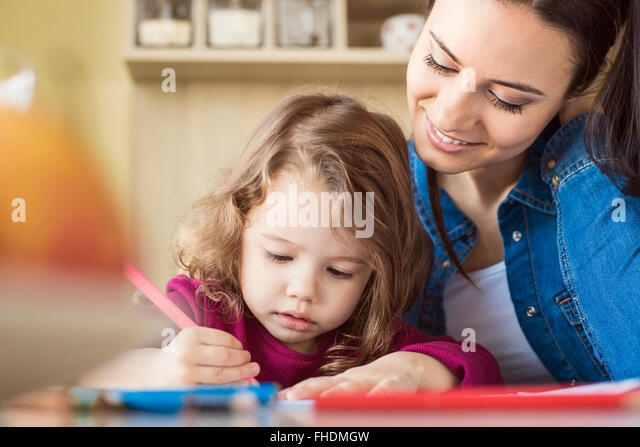 Portrait of little girl painting with coloured pencils while mother is watching her - Stock Image