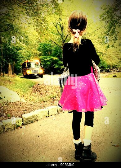 Girl waiting for school bus - Stock Image