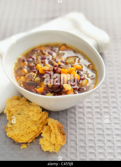 Bowl of adzuki bean vegetable soup served with bread, close-up - Stock Image