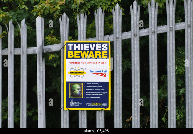 Thieves beware notice alongside railway line, UK - Stock Image