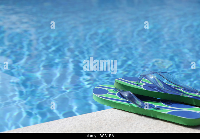 Pair of unbranded flip flops placed at the edga of a swimming pool. - Stock Image
