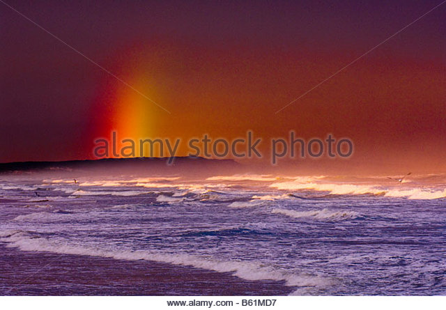 Rainbow behind crashing waves at Strandfontein near Cape Town South Africa - Stock Image