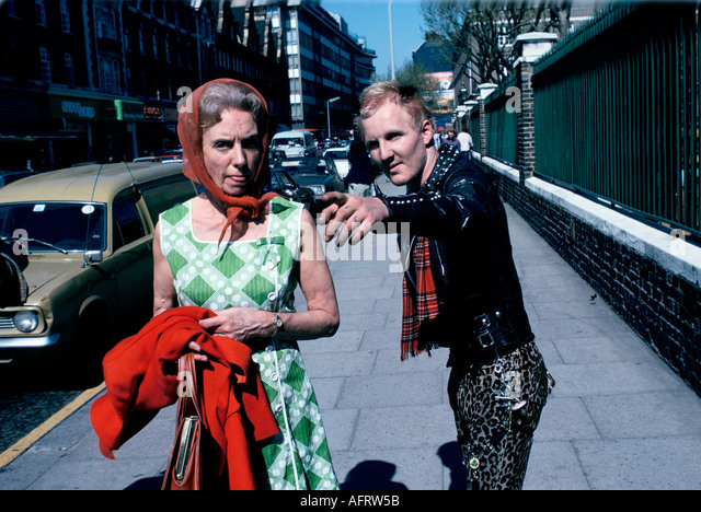 Punk helping passer by on Kings road Chelsea London circa 1975. woman sticking tongue out at photographer HOMER - Stock-Bilder