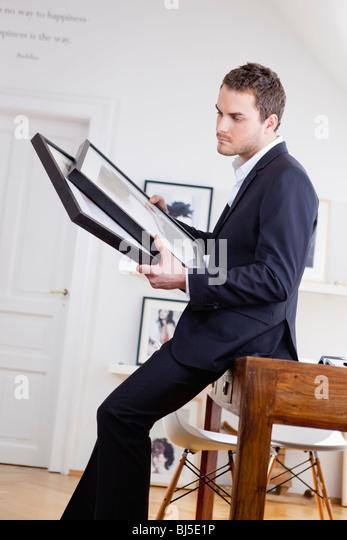 man inspecting paintings - Stock-Bilder