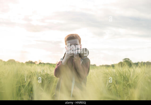 Portrait of a 10 yar old boy taking photographs outdoors - Stock Image