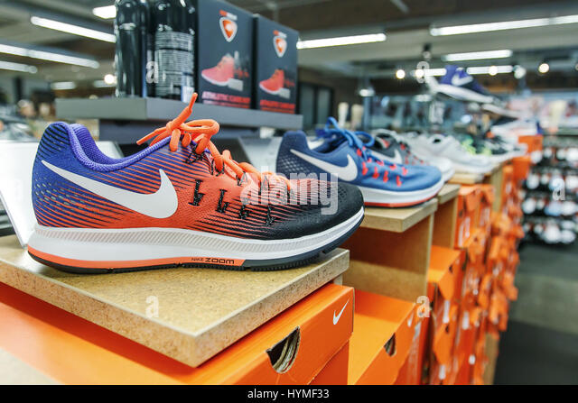Nike shoes are set on display in a shoe store. - Stock Image