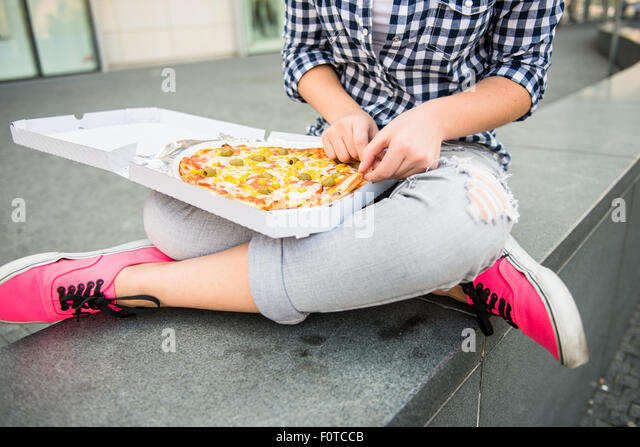 Detail of woman eating pizza outdoor in street - Stock Image