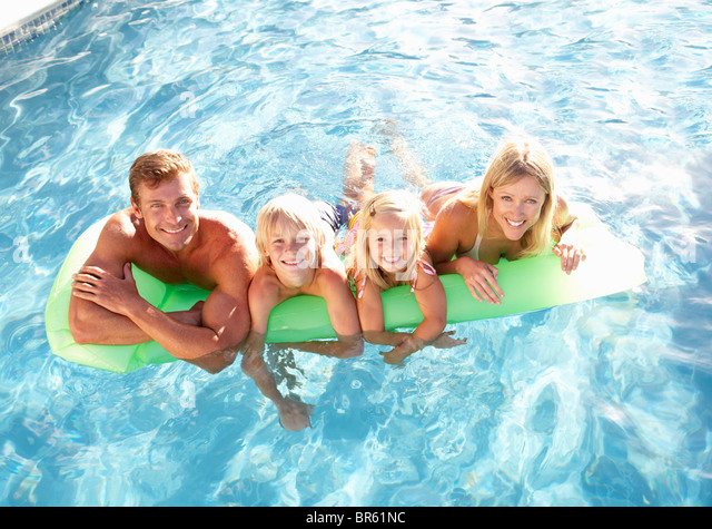 Family Outside Relaxing In Swimming Pool - Stock Image