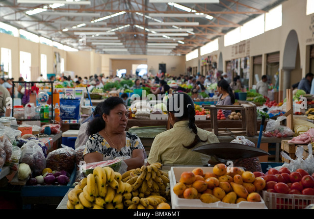 View of Valladolid citys fruit and vegetable main market with two Mexican women at the foreground being surrounded - Stock-Bilder